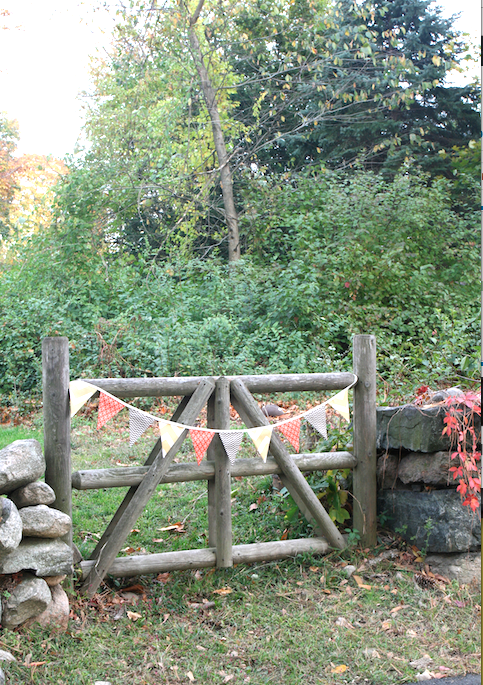 A yard entry signals the season with an autumn colored bunting.