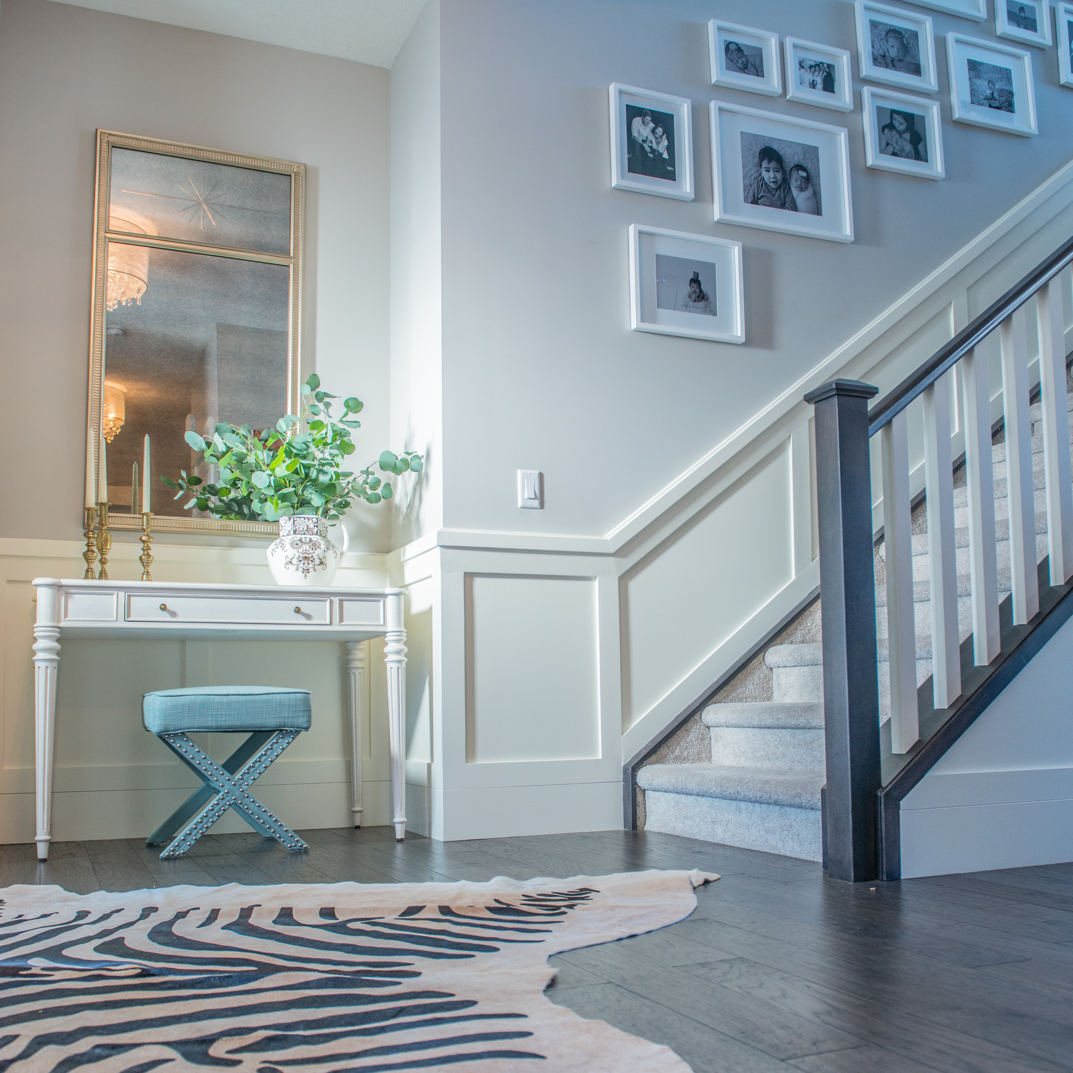 Adding a photo wall, zebra print rug and the right touches of style the entry.